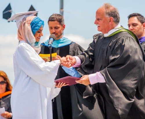 A Walt Whitman High School graduate receives her diploma on Saturday. (Long Islander News photo/Jano Tantongco)