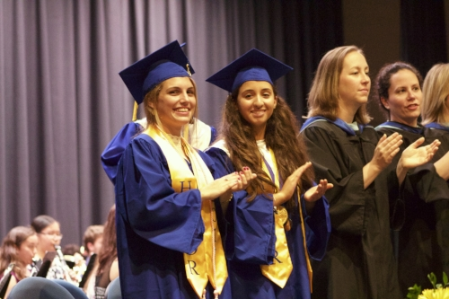 Northport High School valedictorian Cybele Laisney and salutatorian Sarah Abodalo applaud their classmates during the first of Saturday's two ceremonies.  (Long Islander News photo/Janee Law)