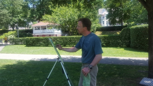 Robert Saal works on his latest chalk piece while enjoying the sun in Northport Village Park on Monday.