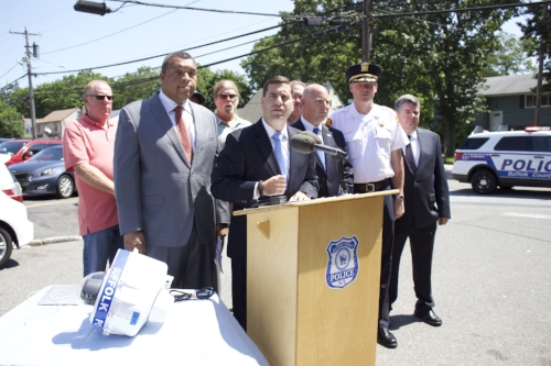 "Long Islander News photo/Janee Law  Suffolk Police Commissioner Timothy Sini, center, is flanked by local officials, including Suffolk Legislator William ""Doc"" Spencer, left, and Suffolk Police 2nd Precinct Inspector Christopher Hatton, right."