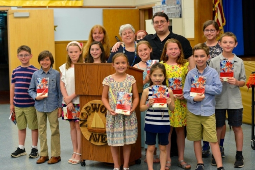 "Photos/Northport-East Northport School District School librarian Linda Trott Dickman and publisher James P. Wagner with Norwood Avenue Elementary School students and their first published book ""Apprentice Poets: Norwood Avenue School, Northport Edition."""