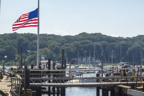 Long Islander News photo/Paul Shapiro The flag at Seymour's Boatyard in Northport Harbor flies at half-staff Wednesday, the day after a 12-year-old Greenlawn boy was killed in a boating accident during a lesson at the Centeport Yacht Club, pictured right-center, across the harbor.