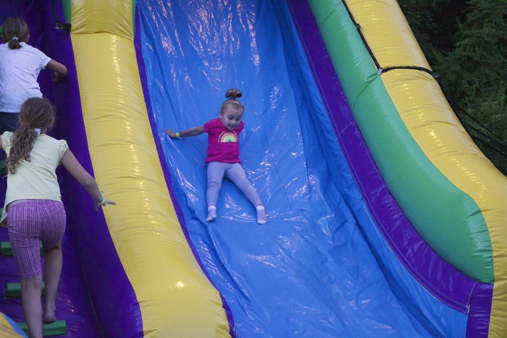 A girl slides down a bouncy house at the 10th Annual Northport Family Fun Night on Tuesday