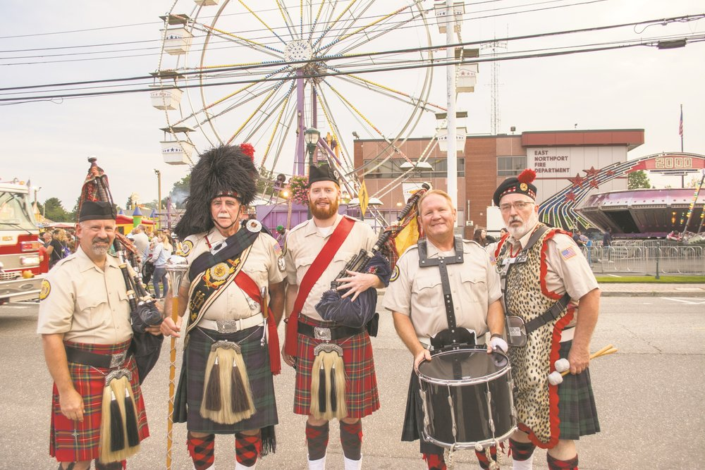 Members of the Amityville Highland Pipe Band are pictured after marching with the Smithtown Fire Department in Wednesday's parade.