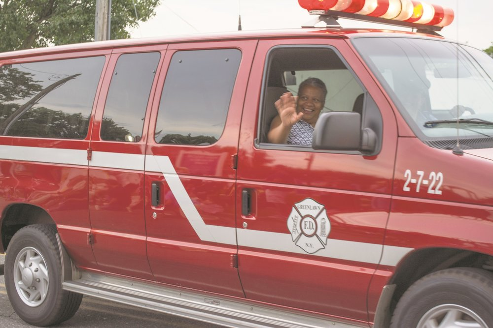 Huntington Councilwoman Tracy Edwards rides in a Greenlawn Fire Department vehicle and waves to the crowd lining Larkfield Road