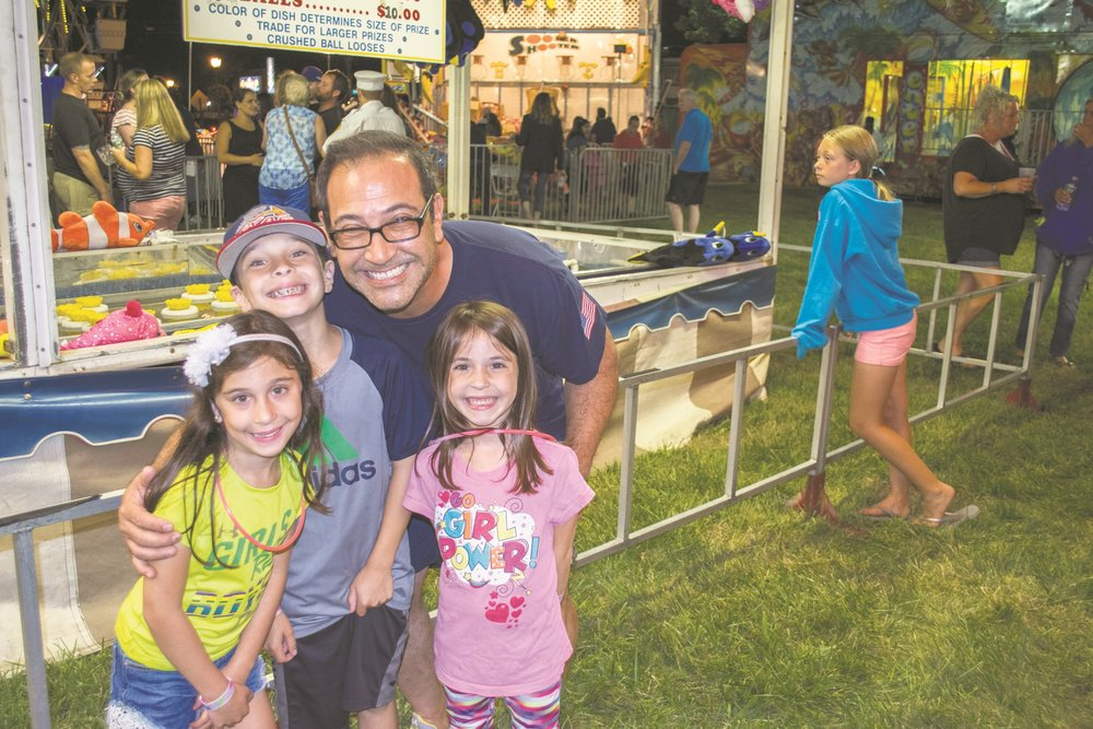 Glenn Lowy, back, and his family are first time attendees at the annual East Northport Fireman's Fair.