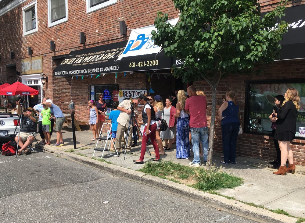Local residents used telescopes set up outside Berger Bros to get a better view of today's solar eclipse.    Long Islander News photo/Paul Shapiro