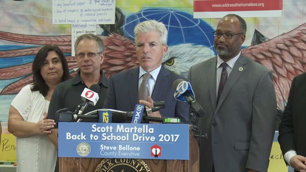 Suffolk Executive Steve Bellone, center, speaks during a back-to-school drive held in memory of the late Scott Martella, a dedicated public servant who was killed in a car crash last summer. Bellone is flanked by Martella's parents, Stacy and Steve, left, and Suffolk Legislature Presiding Officer DuWayne Gregory, right.