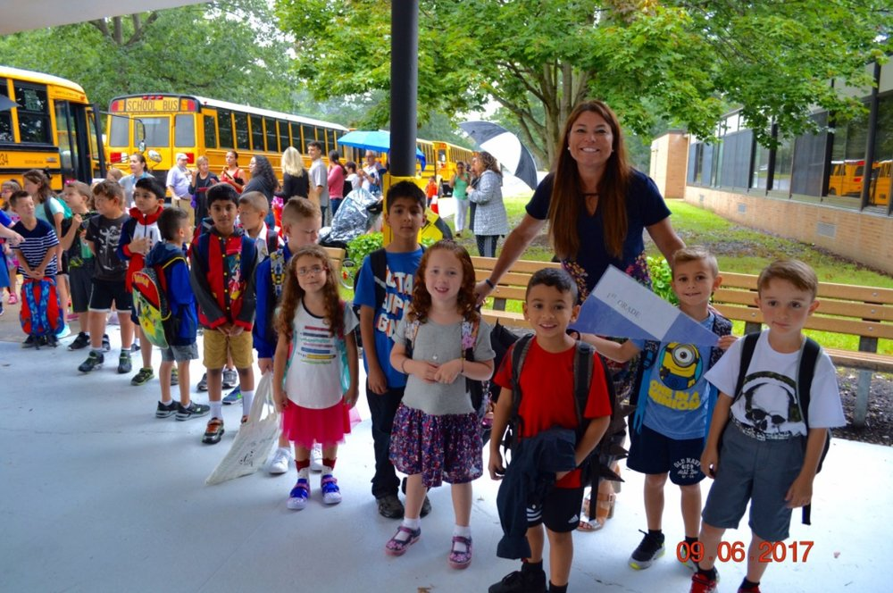 Students of Commack's Wood Park Primary School arrive between the raindrops for their first day.   Photo/Commack School District