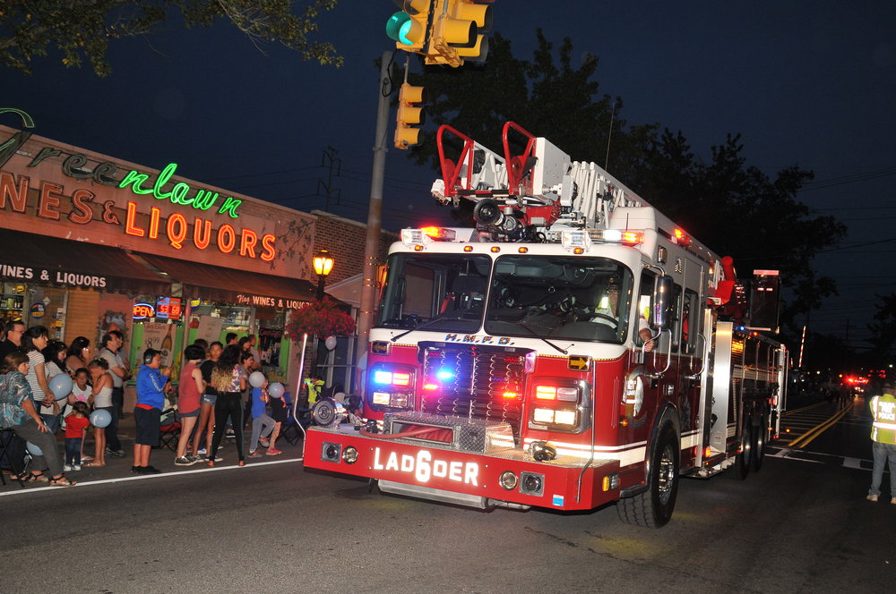 A Huntington Manor Fire Department Ladder Truck is ogled by parade goers.   Photo Courtesy of Steve Silverman