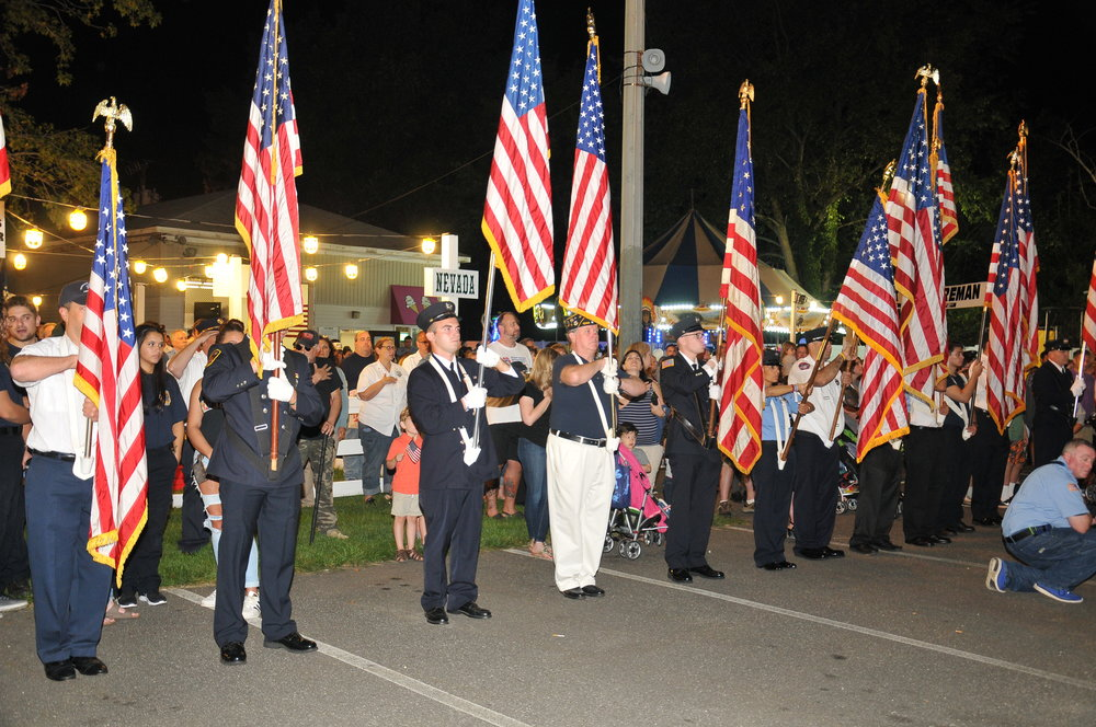 Flags are held high during the playing of the national anthem by the NYPD band.   Photo Courtesy of Steve Silverman