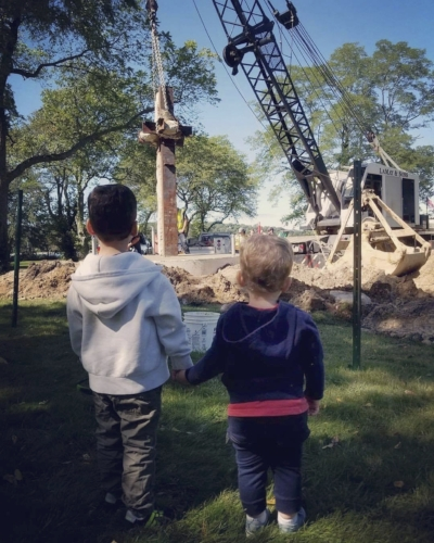 Two children watch as a steel beam from the World Trade Center is added to the 9/11 memorial in   Cold Spring Harbor on Sept. 9.   Photo by Adrian Benvenuti