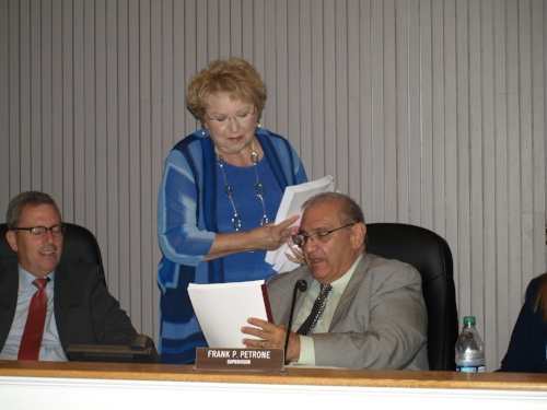 Supervisor Frank Petrone accepts his last budget proposal from Town Clerk Jo-Ann Raia at Tuesday's Town Board meeting. Long Islander News photo/ Connor Beach