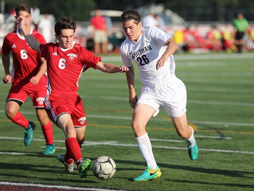 Whitman forward Colin O'Neill, right, runs past a Connetquot defender in a game earlier this season.   Photo Courtesy of South Huntington School District