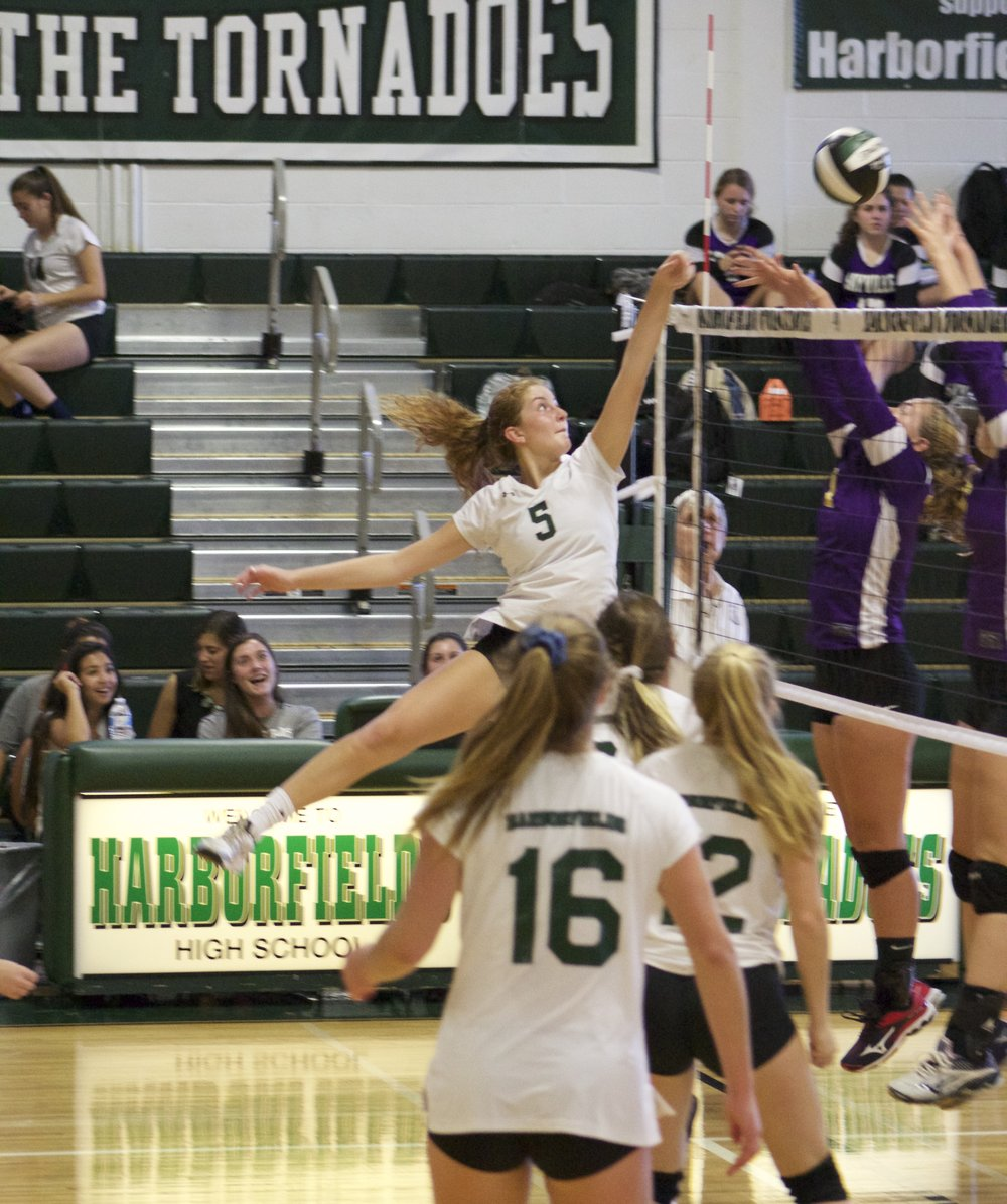 Alex Madden (no. 5) taps the ball over the net during the Harborfields girls volleyball non-league game against Sayville.   Long Islander News Photo/Janee Law