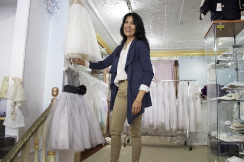 Leah Casabona, owner of Morolay Children's Boutique  , prepares her store for communion season, which runs between November and May -- its busiest time of the year.     Long Islander News Photo/Janee Law