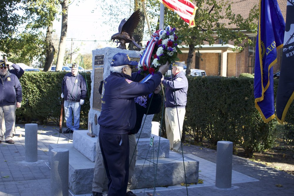One American Legion Greenlawn Post 1244 member places a wreath at the monument during Saturday's ceremony .  Long Islander News Photo/Janee Law