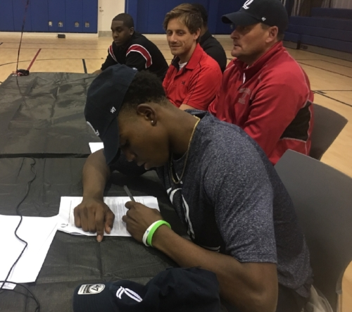 Savion Lewis, a senior basketball player at Half Hollow Hills High School East, inks his National Letter of Intent on Monday, solidifying his commitment to Quinnipiac University.