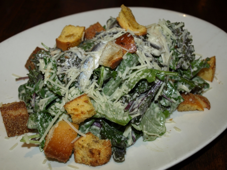 The Baby Kale Caesar ($14) is served with garlic croutons, Parmigiano-Reggiano cheese, marinated white anchovies and a Caesar dressing.   Long Islander News Photo/Connor Beach