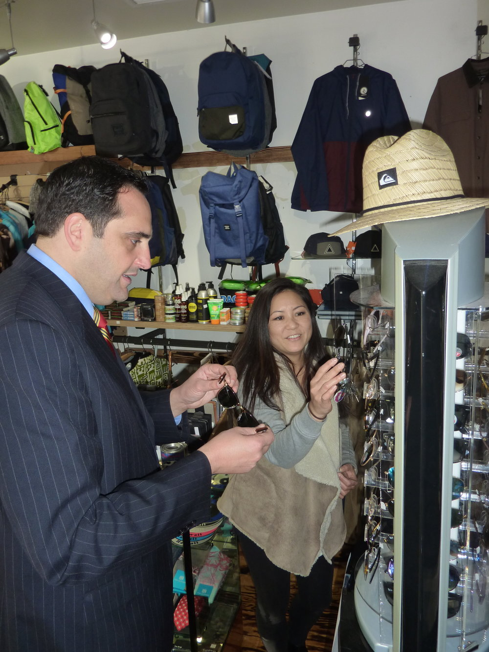 NALU Dry Goods owner Marie Fisher helps Supervisor-elect Chad Lupinacci pick out new shades.   Long Islander News Photo/Peter Sloggatt