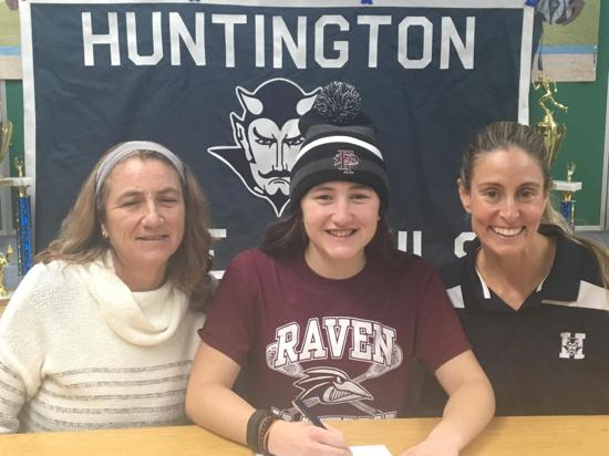 Megan Bacik, center, inks her commitment to Franklin Pierce University in New Hampshire.   Photo Courtesy of Huntington Village Lacrosse Club