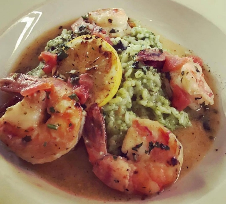 A lunch offering, the Shrimp Scampi at Ruvo in Greenlawn is served over pesto risotto with plum tomatoes and grilled lemon.   Photo/Facebook/Ruvo