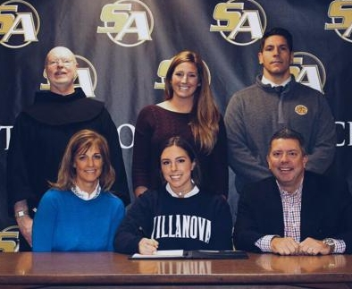 Elizabeth Pawlak, seated center, inks her commitment to Villanova University in Pennsylvania.   Photo Courtesy of Huntington Village Lacrosse Club