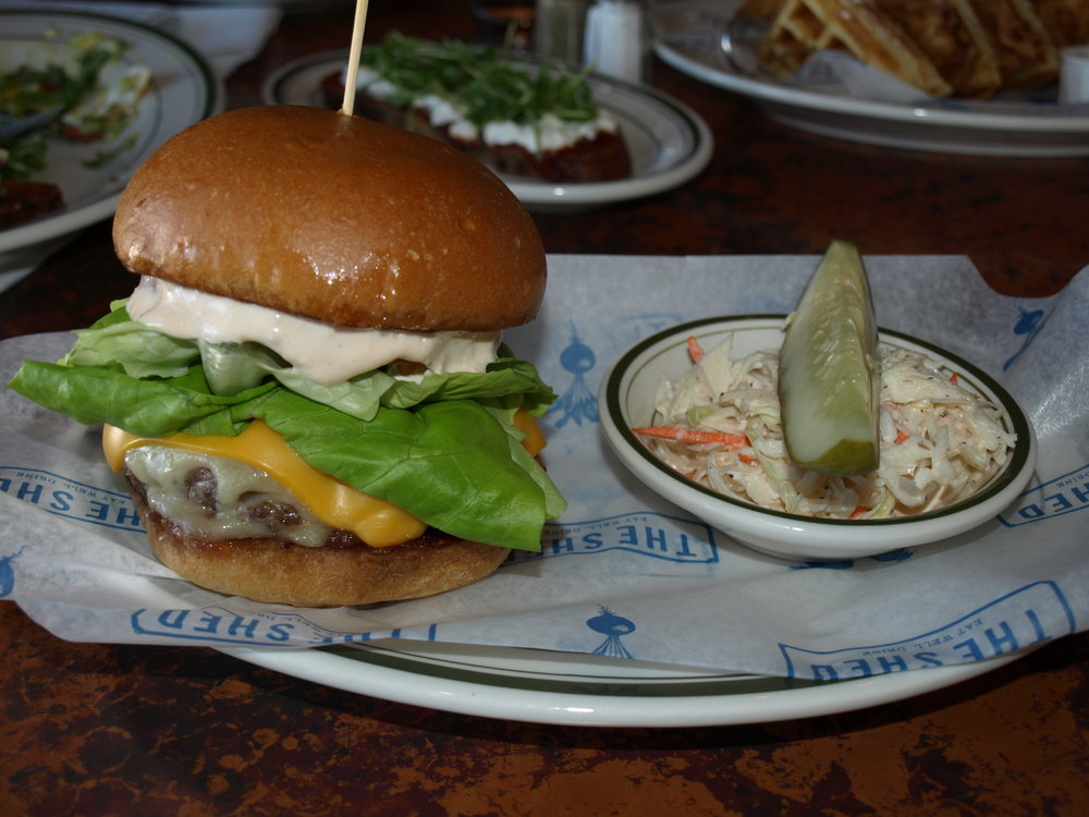 The Shed Burger ($13) is topped with American, Swiss, lettuce, tomato, onion jam and shed sauce and served with a side of coleslaw.     Long Islander News photos/Connor Beach