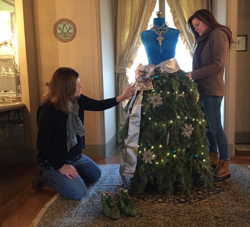 Mary Schlotter and Krishtia McCord, co-owners of Harbor Homestead & Co., put the finishing touches on a Christmas dress created for the dressing room.
