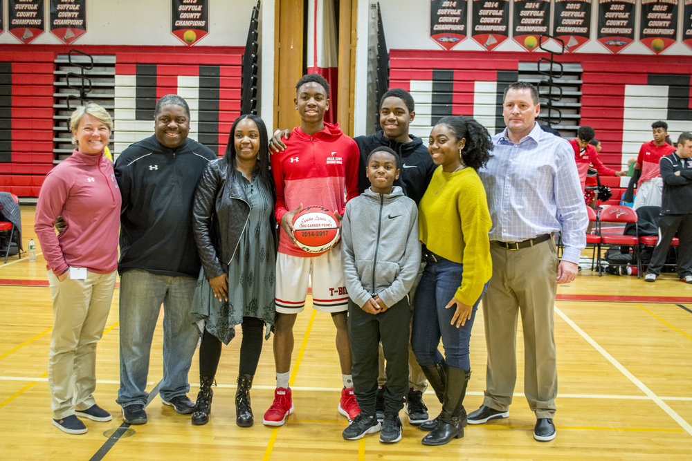 Savion Lewis, center, accepts a basketball commemorating his 1,000th career point, which he scored on Dec. 9. He's joined by his family, coach Peter Basel, right, and Half Hollow Hills Athletic Director Debra Ferry, left.   Long Islander News photo/Andrew Wroblewski