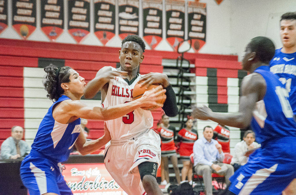 Savion Lewis, right, a senior guard for Hills East, breaks through a North Babylon defender Tuesday night on his way to the basket. He finished with a game-high 34 points.   Long Islander News photo/Andrew Wroblewski