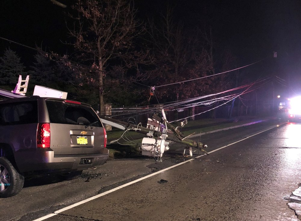 A sports utility vehicle, left, crash into a utility pole, right, Saturday evening in Dix Hills.   Photo/Matt Schwier
