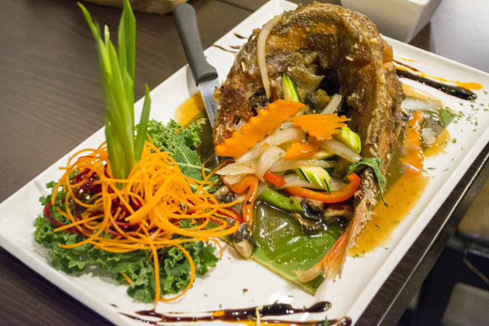 For seafood lovers Tum Thai offers Pla Kra Prow ($23.95) that features red snapper served whole, cooked to a crispy golden brown and topped with chili and Thai basil sauce.   Long Islander News photos/Connor Beach