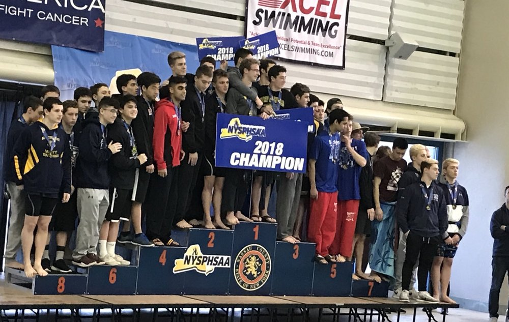 The Half Hollow Hills 200-yard medley relay team of Mason Arnberg, Dylan Chan, Kabir Randhawa and Ethan Tack stand in the fourth-place slot of the podium at the state championships last weekend.   Photo/Twitter