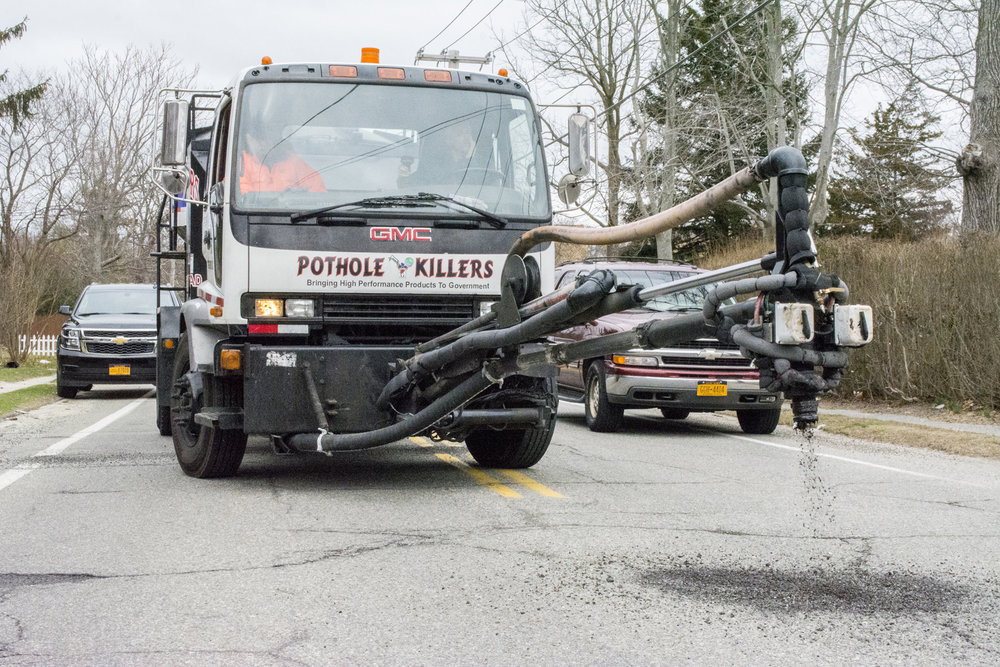 "The crew of the ""Pothole Killer"" demonstrates the truck's method to quickly fill potholes on the corner of Fort Salonga Road and Laurel Road in Northport.   Long Islander News photo/Connor Beach"