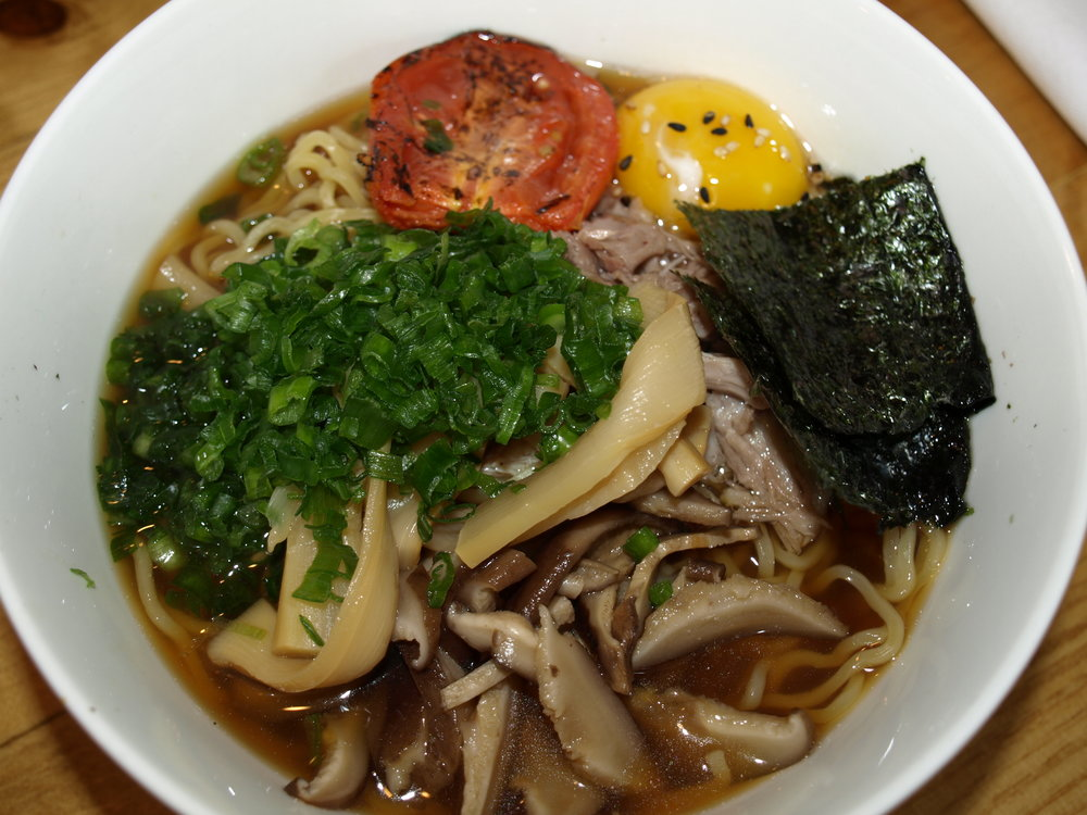 Shoyu Ramen ($13), above, brings together duck confit, menma, scallion, nori seaweed, oven roasted tomato, egg yolk and a wavy noodle.