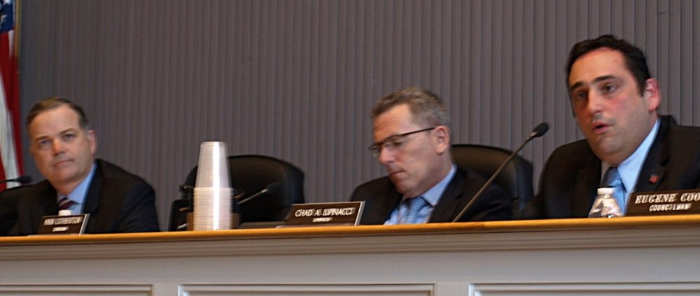 Councilman Ed Smyth, left, questions Tuesday the board's decision to convey a 0.5-acre property in Huntington Station to developer Renaissance Downtowns so that the developer can move forward with its area revitalization project.   (Long Islander News photo/Connor Beach)