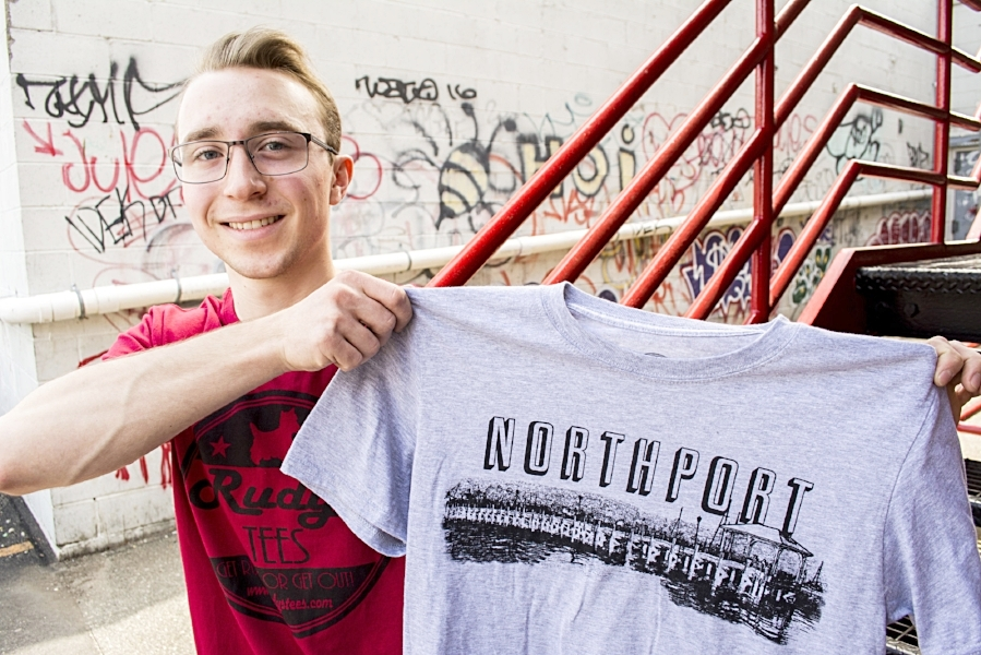 Brandon DeFeo, 19, with one of Rudy's Tee's custom historical shirts featuring Northport pier.   (Long Islander News photo/Andrew Wroblewski)