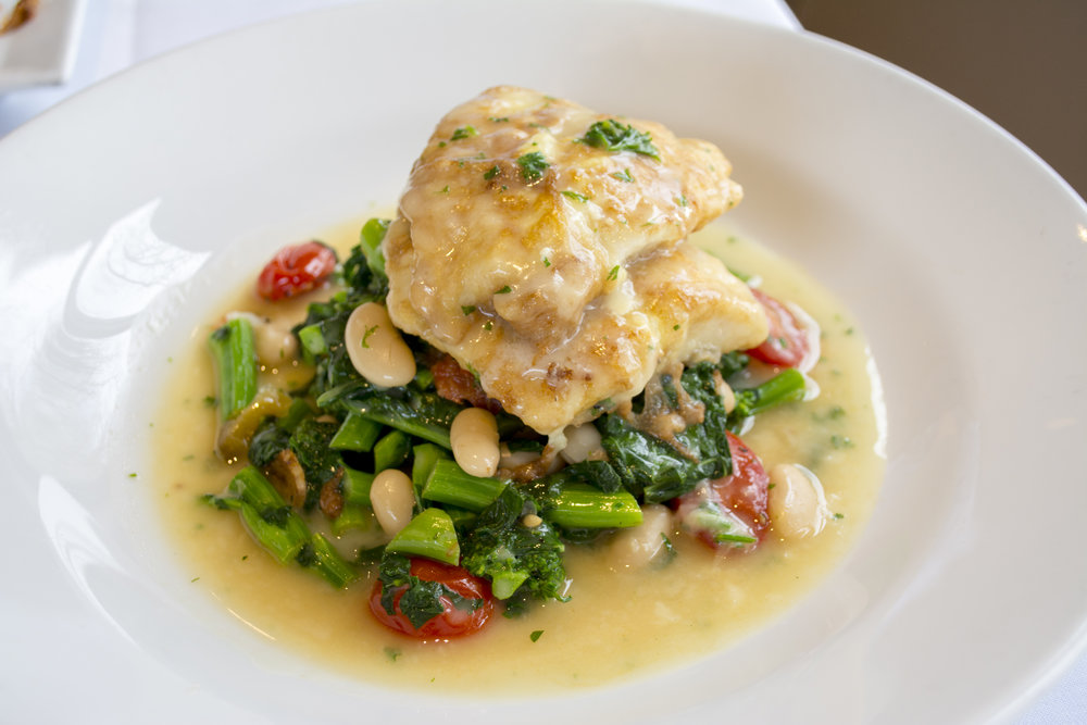 Red Snapper Francaise served over broccoli rabe, white beans and cherry tomatoes in a lemon butter sauce.