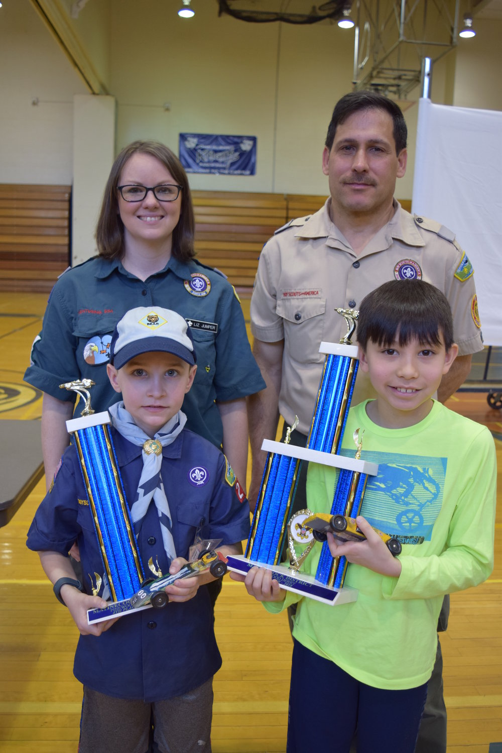 Jack R., front-left, and Evan A., front-right, of Greenlawn's Pack 225 placed fourth and third respectively in last weekend's races. They're pictured with their trophies and hand-crafted pinewood derby racecars.