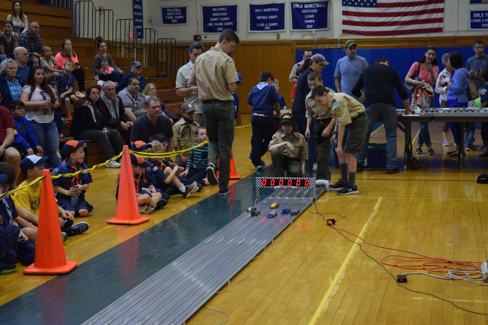 """Cub Scouts and their parents watch the racecars as they near the end of the runway and the """"pit crew"""" Boy Scouts get ready to retrieve the cars at the end of the track."""