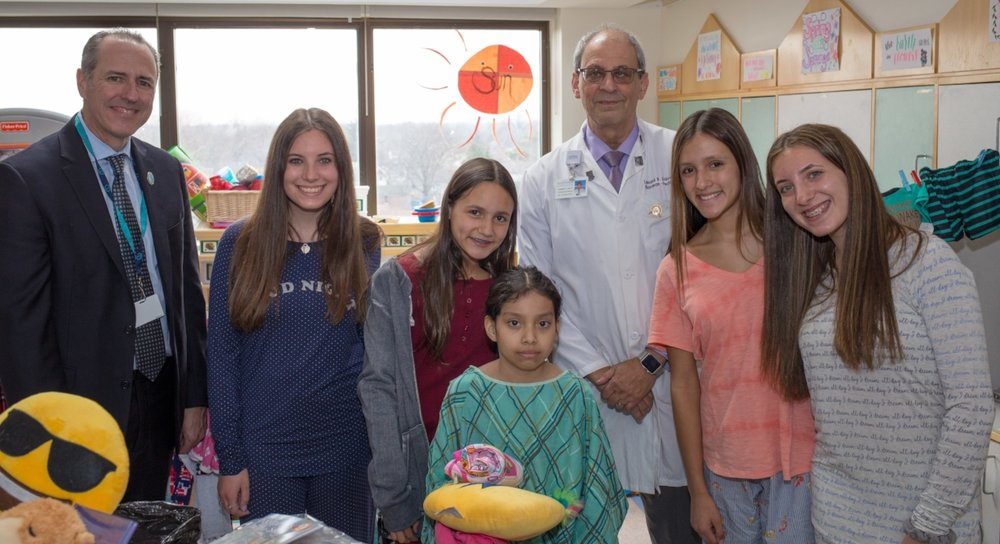 Pictured above at the Children's Medical Center at NYU Winthrop Hospital are, from left: Half Hollow Hills Superintendent Dr. Patrick Harrigan; student organizers Hayley Kalb and Marissa Mandel; patient   Mareli Galindo; NYU Winthrop Chairman of Pediatrics Dr. Leonard Krilov; and student organizers Morgan Mandel and Ashley Kalb.   (Photo/Half Hollow Hills)