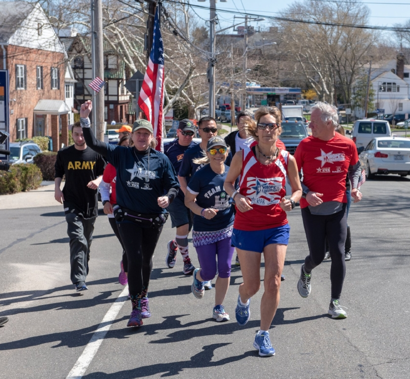 Eva Casale, front-center, begins the first of her seven marathons in seven days to raise money and awareness for veterans on Main Street in Huntington.   (Photo/Alyssa Nightingale)