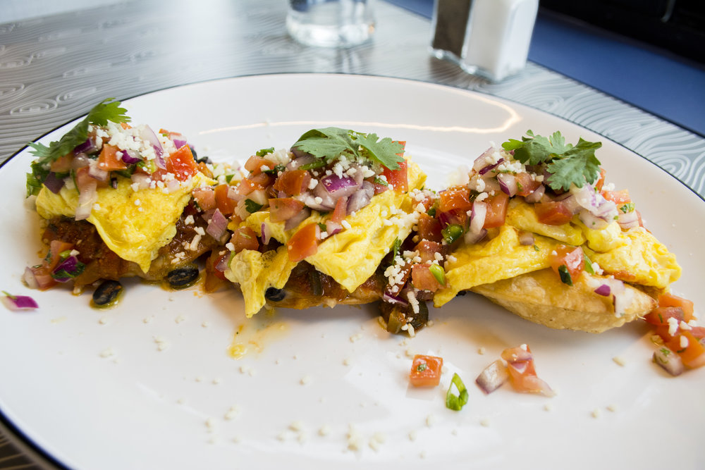 The Huevos Rancheros ($11.25) starts with crisp corn tortillas layered with black beans, jack cheese, ranchero sauce, three eggs any style, salsa fresca and cotija cheese.
