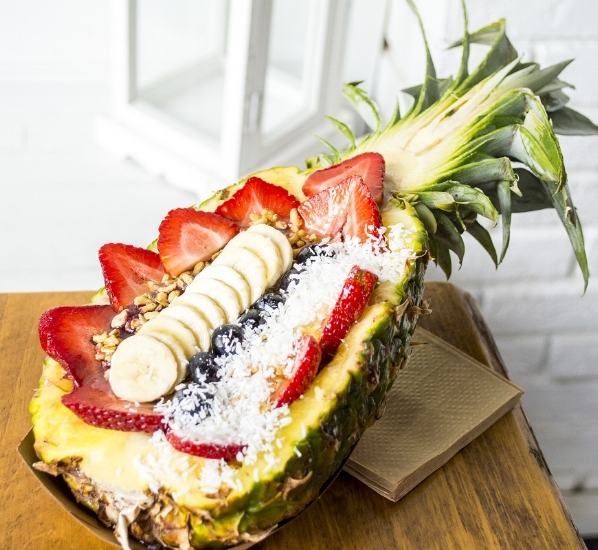 The Acai Smoothie Bowl, above, is served in a pineapple ($13). It features organic acai blended with strawberries, blueberries and banana and is topped with strawberries, blueberries, banana, granola, coconut and honey.   (Long Islander News photos/Connor Beach)