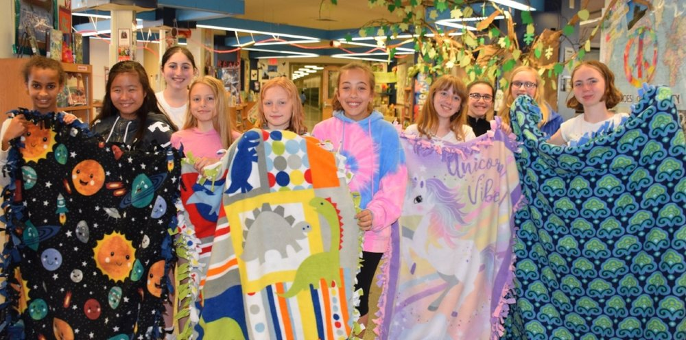 Students at Oldfield Middle School recently gave back to the community by giving up portions of their homerooms and recesses to create fleece blankets to donate to Project Linus.   (Photos/Harborfields)
