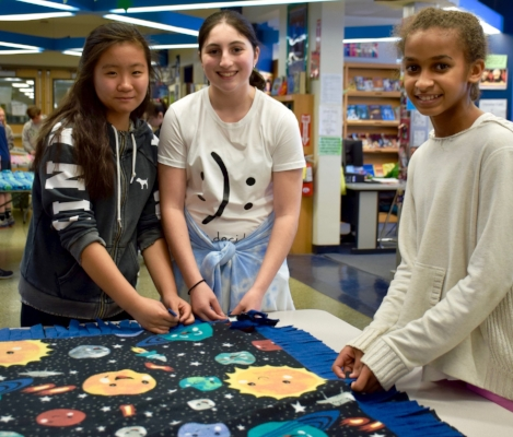 Right: Oldfield Middle School students Hanna, Journey and Aryana work together to assemble fleece blankets to donate to Project Linus.