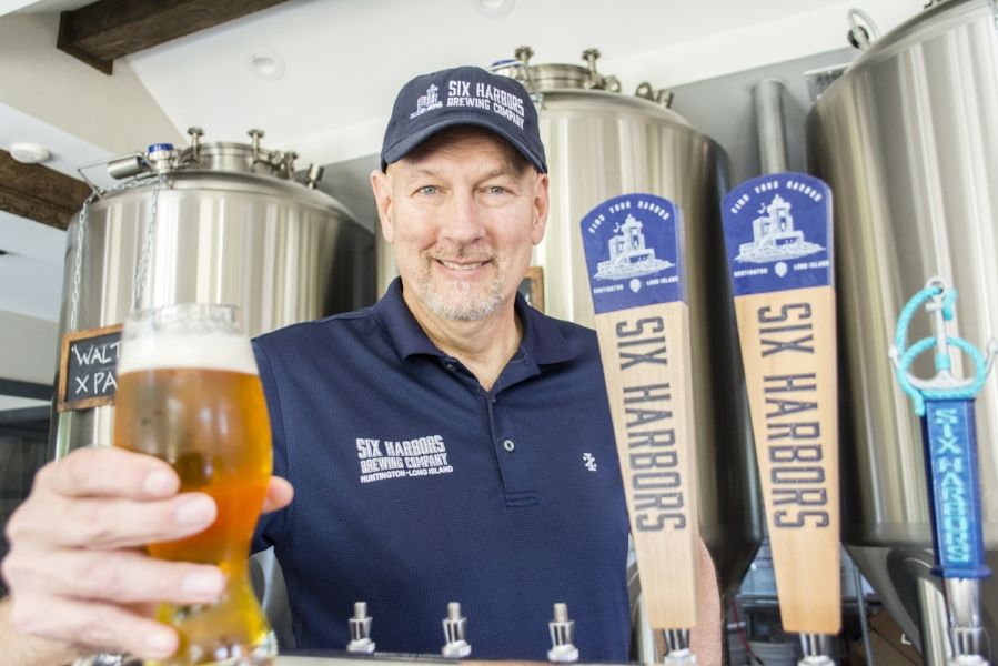 Mark Heuwetter serves up a pint of the Young Professionals Ale at his newly-opened Six Harbors Brewing Company – Huntington village's first craft brewery.   (Long Islander News photo/Andrew Wroblewski)