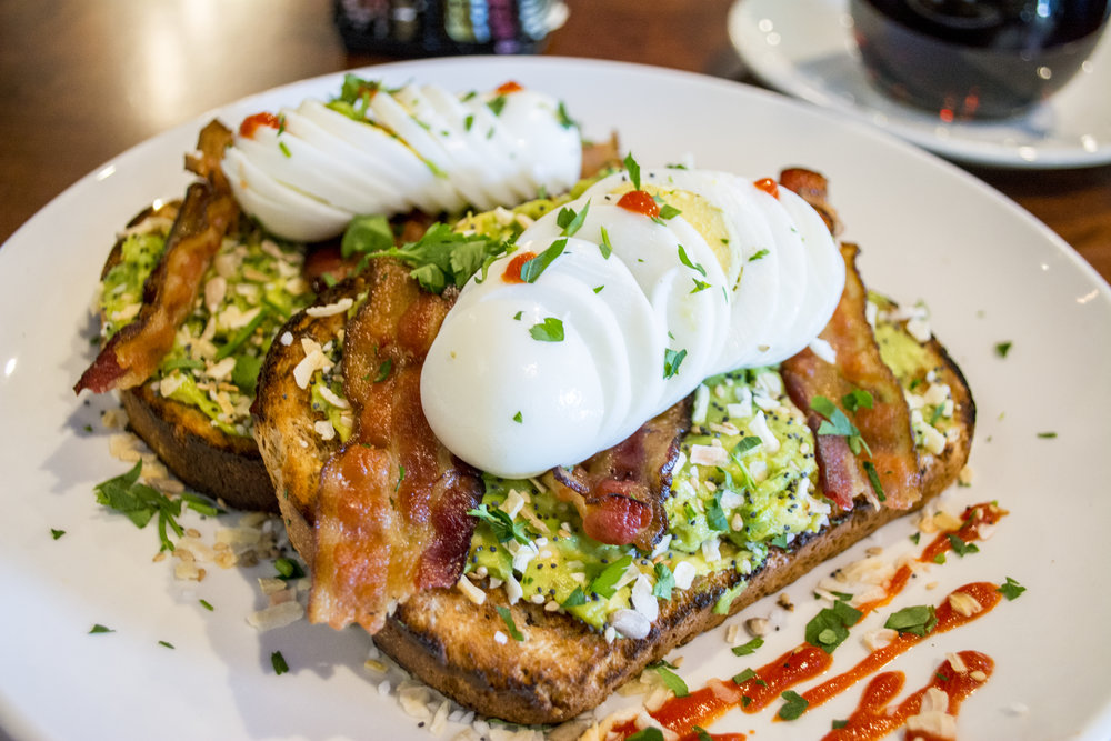 Everything Seed Bacon Sriracha Avocado Toast ($12.99) includes fresh avocado spread, bacon, sliced hard boiled eggs, everything bagel seeds mix and Sriracha on multigrain toast.