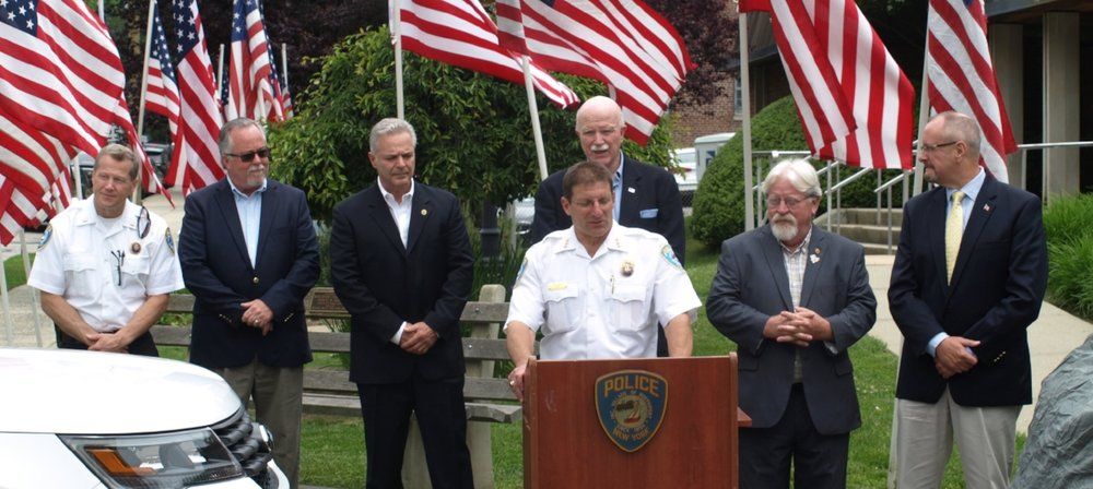 Northport Village Police Chief Bill Ricca, standing at podium, speaks Friday at an event signifying the donation of an undercover police vehicle to the department. Standing with Ricca, from left, are: Northport Village PD Lt. Michael Cook; Kevin Gallagher, director of field operations for the northeast region of NICB; Gerard LaRocco, of MetLife; Northport Village Deputy Mayor Thomas Kehoe; Northport Village Mayor Damon McMullen; and John Sargent, MetLife national director of investigations.   (Long Islander News photos/Joseph Marasciullo)